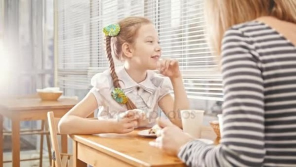 Girl With Pigtail Eats Sweet Cakes And Talks With Her Mum In The
